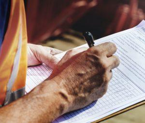 Image of a person completing a legionella or asbestos safety checklist